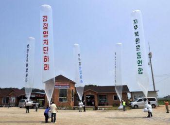 Северокорейские диссиденты запускают в Северную Корею большие воздушные шары с антипхеньянскими листовками  в демилитаризованной зоне, разделяющей две Кореи в Канхвадо, в 60 километрах севернее Сеула. 3 июля 2003 г. Фото: Jung Yeon-Je /AFP /Getty Images