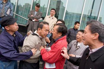 Фу Ни (в красной куртке) нападает на Бунн Тион Ерха напротив библиотеки Квинса во Флашинге 20 мая 2008 г. Фото: Великая Эпоха