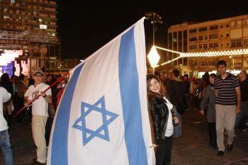 Молодой человек размахивает большим флагом Израиля на улицах Тель-Авива. Фото: Яйра Ясмин/ Великая эпоха