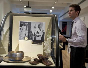 Служащий Аукционного дома показывает выставленные на продажу круглые очки Махатмы Ганди, его часы и сандалии. Фото: DON EMMERT/AFP/Getty Images