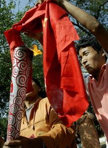 Тибетец поджигает флаг КНР на этафетном факеле в знак протеста. Фото: CHRISTOPHE ARCHAMBAULT/AFP/Getty Images