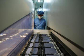24 июня 2009 года рабочий проверяет линию продукции силиконовых чипов, используемых в производстве фотоэлектронных табло на заводе Tianwei Yingli Green Energy Resources Co., Ltd в Баодине, Китай. Фото: Feng Li/Getty Images