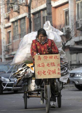 Женщина едет по одной из улиц Пекина на велосипеде, загруженном материалами для повторной переработки. Фото: Liu Jin /AFP /Getty Images
