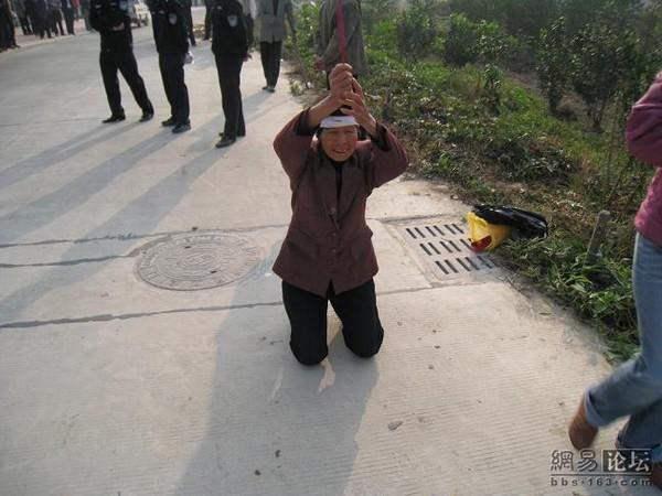 Крестьянка на коленях просит чиновников не забирать у неё землю. Фото с epochtimes.com