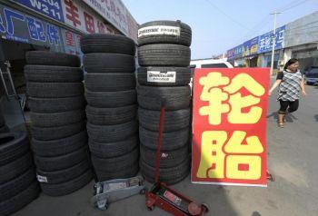 Женщина проходит мимо шин, выставленных на продажу в Пекине 14 сентября. Китай выразил недовольство тарифами США на экспорт шин и объявил, что проведёт расследование с целью обнаружения возможных незаконных приёмов в экспорте США, обостряя этим и без того натянутые отношения. Фото: LIU JIN/AFP/Getty Images