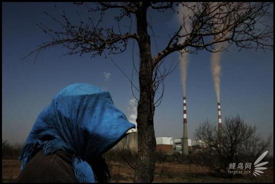 Местные жители промышленного района Хубинь города Шисуйшен провинции Нинся, выходя на улицу, закутывают голову и лицо от частиц пыли падающих из дымовых труб местных предприятий. 22 апреля 2006 год. Фото: Лу Гуан