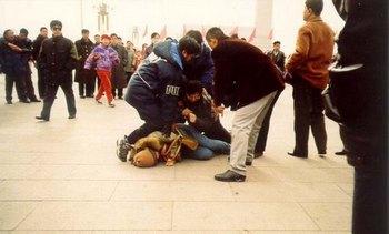 Сотрудники китайских служб безопасности арестовывают последовательницу Фалуньгун. Фото с epochtimes.com