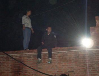 Полицейские залезли на забор и сказали, что если их не впустят через дверь, то они залезут в квартиру через окно. Фото с minghui.org