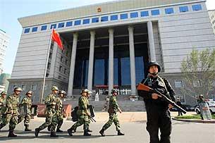 Вооружённые полицейские охраняют здание суда в Синьцзяне, в котором судят участников беспорядков. Фото: RFA