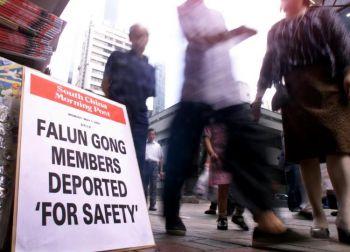 Люди проходят мимо стенда новостей с объявлением о депортации двух практикующих Фалуньгун