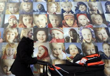 Молодая мама с ребенком на фоне панно с многочисленными портретами детей Рейкьявика. Фото: Olivier Morin/AFP/Getty Images