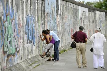 Остатки Берлинской стены с 1989 года, на западной стороне, протяженностью в 1,3 километра используется для рисунков и памятных надписей. Фото: JOHN MACDOUGALL/AFP/Getty Images