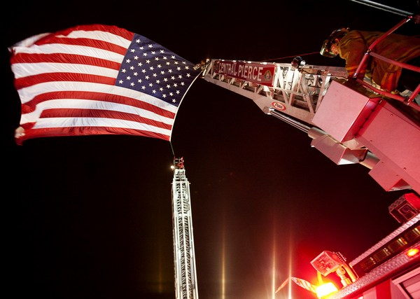 Пожарный снимает флаг после того, как процессия увезла  тела четырех Лейквудских полицейских. Фото: Stephen Brashear/Getty Images)