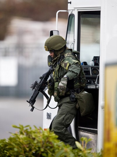 Член команды ОМОН выходит из грузовика, ища подозреваемого 29 ноября 2009 около Лейквуда, Вашингтона. Фото: Stephen Brashear/Getty Images
