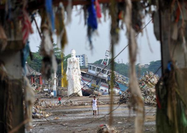 Строения вдоль реки Марикина и большая статуя после урагана Кетсан в Маниле  (29.09.2009). Фото: TED ALJIBE/AFP/Getty Images