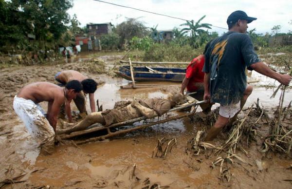 Жители перевозят потерпевшего от урагана  в городе Кьезон в Маниле (27.09.2009). Фото:  STR/AFP/Getty Images