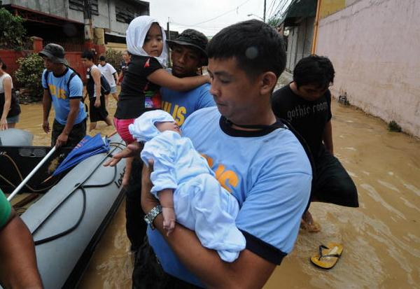 Спасатели переносят в лодку детей в городе Пассиг в Маниле (27.09ю2009). Фото:  MIKE CLARKE/AFP/Getty Images