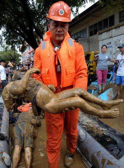 Спасатель несёт тело погибшего ребёнка. Фото: JAY DIRECTO/AFP/Getty