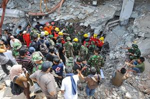 Спасатели разыскивают под обломками людей. Фото: ROSLAN RAHMAN/AFP/Getty Images