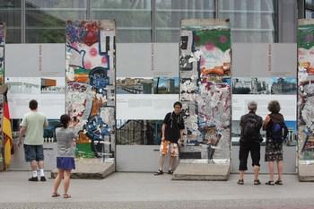 Люди смотрят на мемориал из остатков берлинской стены. Фото: Sean Gallup/Getty Images