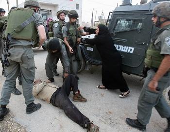 Палестинская женщина останавливает израильтянских солдат. Фото: JAAFAR ASHTIYEH/AFP/Getty Images