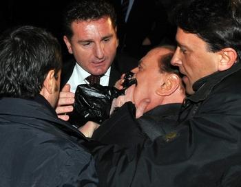 Получив удар, Берлускони упал, после чего сопровождавшие его люди помогли ему подняться. Фото: LIVIO ANTICOLI/AFP/Getty Images