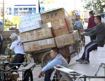 На улице китайского города Хэйхэ. Русский торговец помогает удержать тележку. Фото: GOH CHAI HIN/AFP/Getty Images