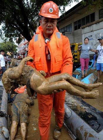 Спасатель  несёт тело погибшего ребёнка. Фото: JAY DIRECTO/AFP/Getty Images