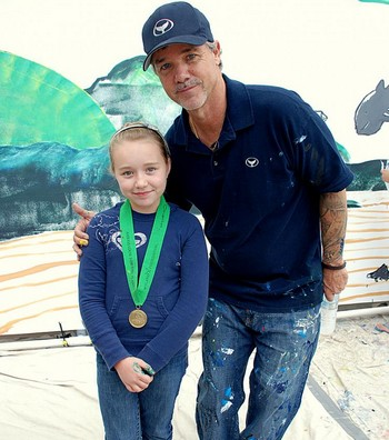 Медаль за освещение: Лилли, 9 лет, ее наградили медалью Уайленда, она позирует с художником. Фото предоставлено Мириам Moран