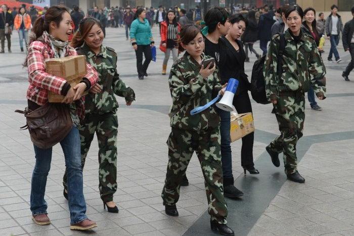Девушки в форме идут по центральной улице Чунцина 4 февраля 2013 года, несмотря на недавнее заявление, что специальный женский отряд полиции, созданный опальным Бо Силаем, будет распущен. Фото: MARK RALSTON/AFP/Getty Images