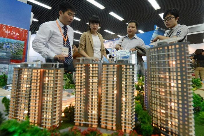 Люди рассматривают продаваемую недвижимость на модели микрорайона Пекина. Инвестиционная выставка, 20 сентября 2012 года. Фото: MARK RALSTON/AFP/GettyImages