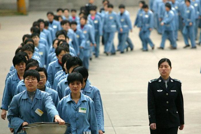 Заключённые под наблюдением охраны в тюрьме Нанкина, Китай, 11 апреля 2005 года. Призывы к ликвидации системы трудовых лагерей растут в Китае с каждым днём. Фото: STR/AFP/Getty Images