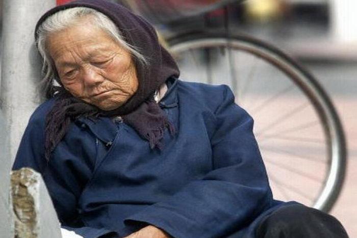 Пожилая женщина лежит рядом с пешеходной эстакадой в Пекине. Фото: Frederic J.Brown/AFP/Getty Images