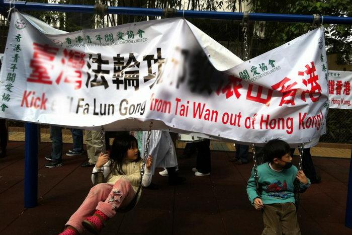 Дети катаются на качелях, к которым Ассоциация содействия молодёжи Гонконга прицепила свой баннер с нападками на Фалуньгун. На заднем плане — другой их баннер. Фото: The Epoch Times