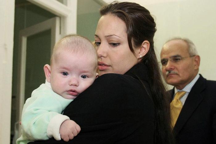 Анджелина Джоли держит ребенка на руках. Фото: Tanya Makeyeva-UN Pool/Getty Images