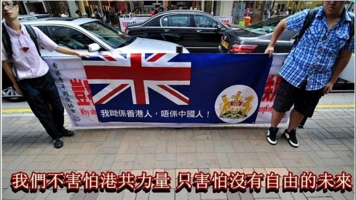 13 ноября 2012 года 2 члена группы «Мы, гонконгцы — не китайцы» держали баннер, на котором изображён колониальный флаг и по-китайски написано: «Мы не боимся коммунистической власти в Гонконге. Мы боимся потерять свободное будущее». Своим баннером они закрыли баннер Ассоциации содействия молодёжи Гонконга. Фото с сайта theepochtimes.com