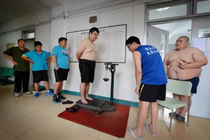 Люди с ожирением проверяют свой вес после иглоукалываний и физических упражнений в «Аймине», центре по снижению веса в северном портовом городе Тяньцзинь, Китай, 14 июня 2012 года. Фото: Mark Ralston/AFP/Getty Images