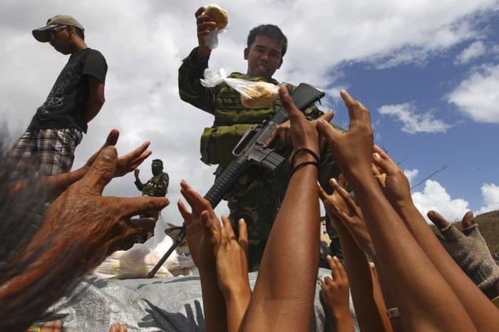 Филиппинский солдат раздаёт хлеб оставшимся в живых после тайфуна Хайянь, Марабут, Филиппины, 14 ноября 2013 года. Фото с сайта theepochtimes.com
