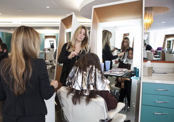Колорист Николь Трэш наносит краску и заворачивает в фольгу волосы писательницы Елены Маркс. Фото: Samira Bouaou/Великая Эпоха (The Epoch Times)