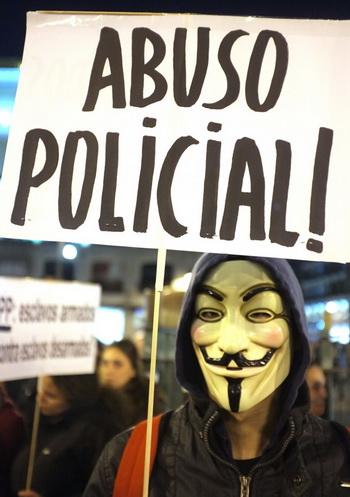 Демонстрант в популярной маске Гая Фокса на фоне баннера: «Долой произвол полиции!», площадь Пуэрта-дель-Соль, Мадрид, 21 февраля. Фото: Dominique Faget/AFP/Getty Images