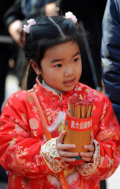 3 февраля 2011 года.  Гонконг, В первый день Нового года, маленькая девочка держит палочки с предсказаниями. Фото: Mike Clarke/AFP/Getty Images
