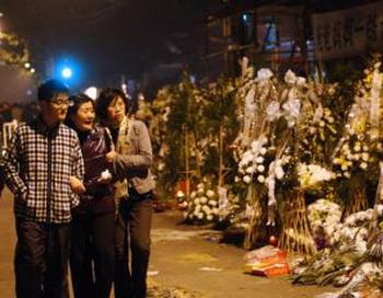 Члены семьи скорбят по погибшим 21 ноября при пожаре высотного здания в Шанхае. Фото: STR/Getty Images