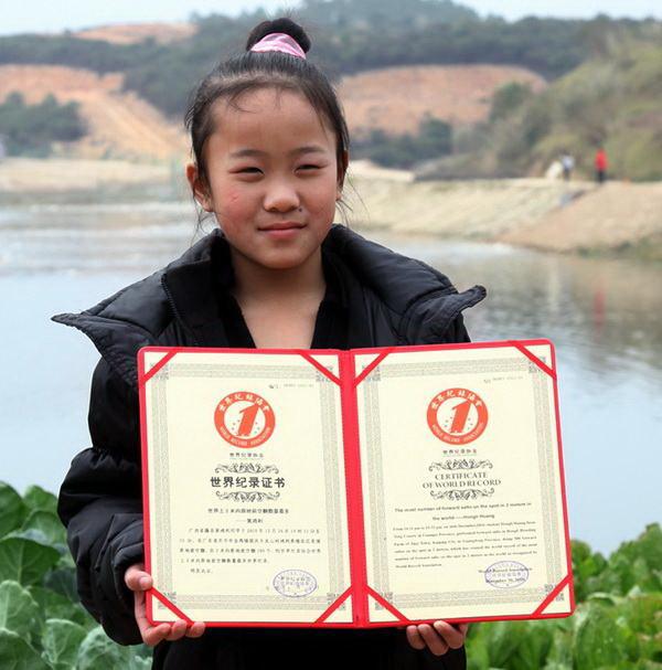 Девочка держит в руках диплом о мировом рекорде. Фото: kaiping.gov.cn