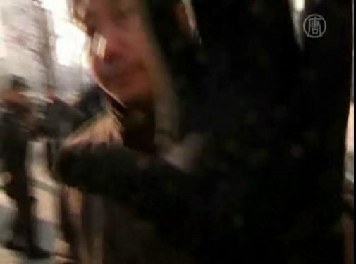 Сотрудник спецслужб в штатском закрывает рукой камеру, запрещая снимать арест апеллянтов напротив офиса CCTV в Пекине. Фото: NTD