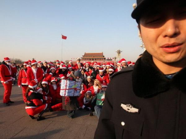 Безобидное развлечение и совместная фотография на площади Тяньаньмэнь в Пекине послужило поводом для полиции выпроводить 100 Дедов Морозов как нарушителей порядка. Фото: STR/AFP/Getty Images