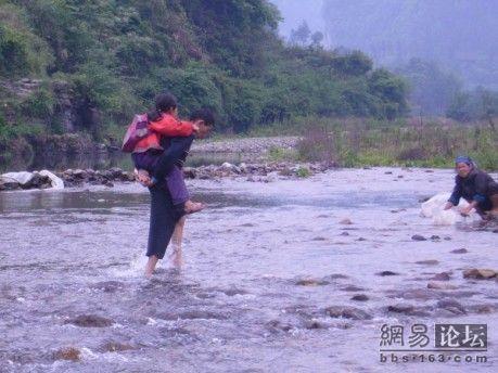 Некоторые дети слишком маленькие и учителю после уроков приходится по одному переносить их через реку. Фото с secretchina.com