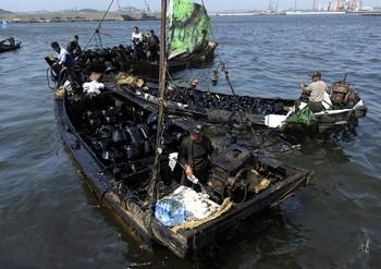 Местные жители вылавливают нефть из Жёлтого моря. Фото: LIU JIN/AFP/Getty Images