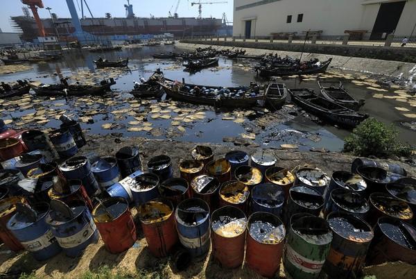 Рыбаки вылавливают нефть из Жёлтого моря. 25 июля 2010 год. Фото: AFP