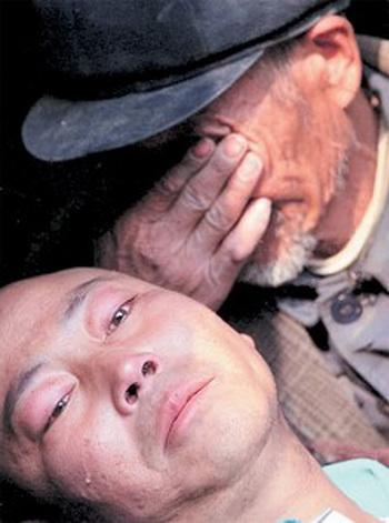 Отец плачет над умирающим от СПИДа сыном.Фото:AFP