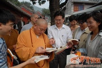 Ши Юнсин, настоятель монастыря Шаолинь, оставляет автографы туристам на память. Фото с сайта epochtimes.com